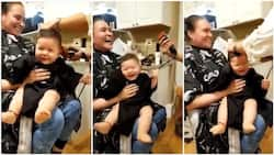See the reaction of this baby at barbing salon getting haircut, instead of crying, this was what he did to the clipper (video)