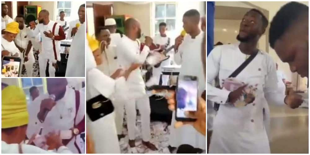 Video shows family members spraying cash on a male chorister in church, people watch them in surprise