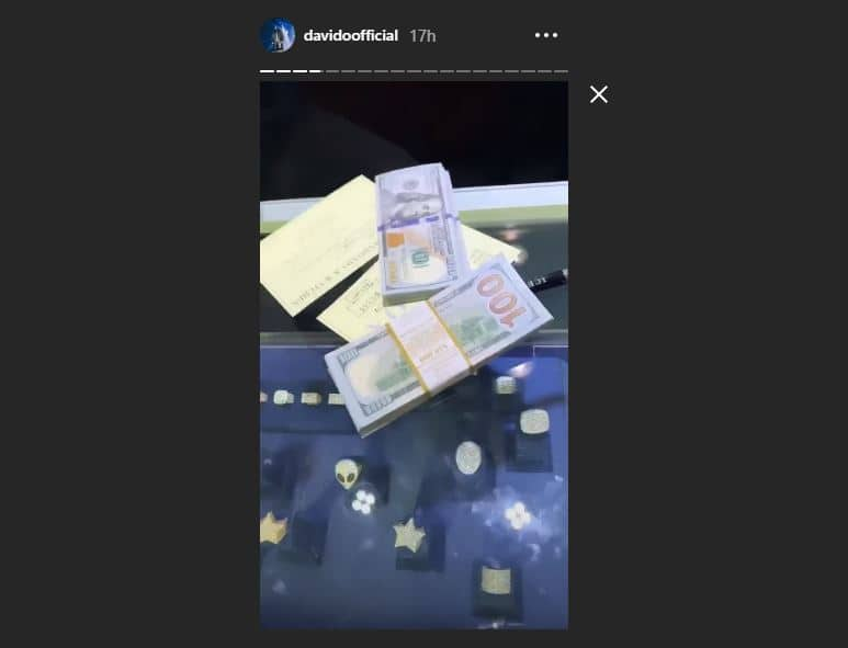 Davido shows off his expensive, diamond-encrusted accessories and dollar bills (video)
