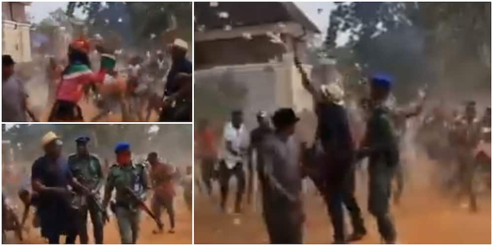 Reactions as masquerade, others jostle to pick cash as man sprays money on street in video
