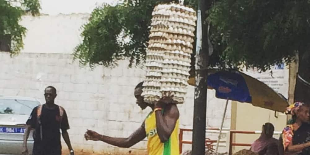 Man Shows Incredible Strength & Skill as He Walks on Wet Ground While Carrying Loads of Eggs on One Arm