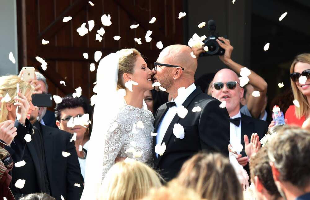 Le chanteur français Pascal Obispo (à droite) et la mannequin Julie Hantson s'embrassent devant l'église du Cap Ferret après leur mariage le 19 septembre 2015.