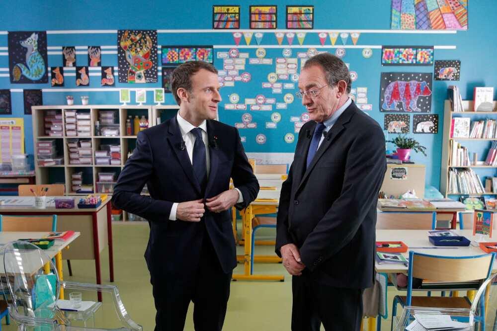 Le président français Emmanuel Macron (à gauche) s'entretient avec le journaliste français Jean-Pierre Pernaut (à droite) après avoir été interviewé à l'intérieur de la salle de classe sur la chaîne de télévision française TF1 à l'école de Berdhuis.