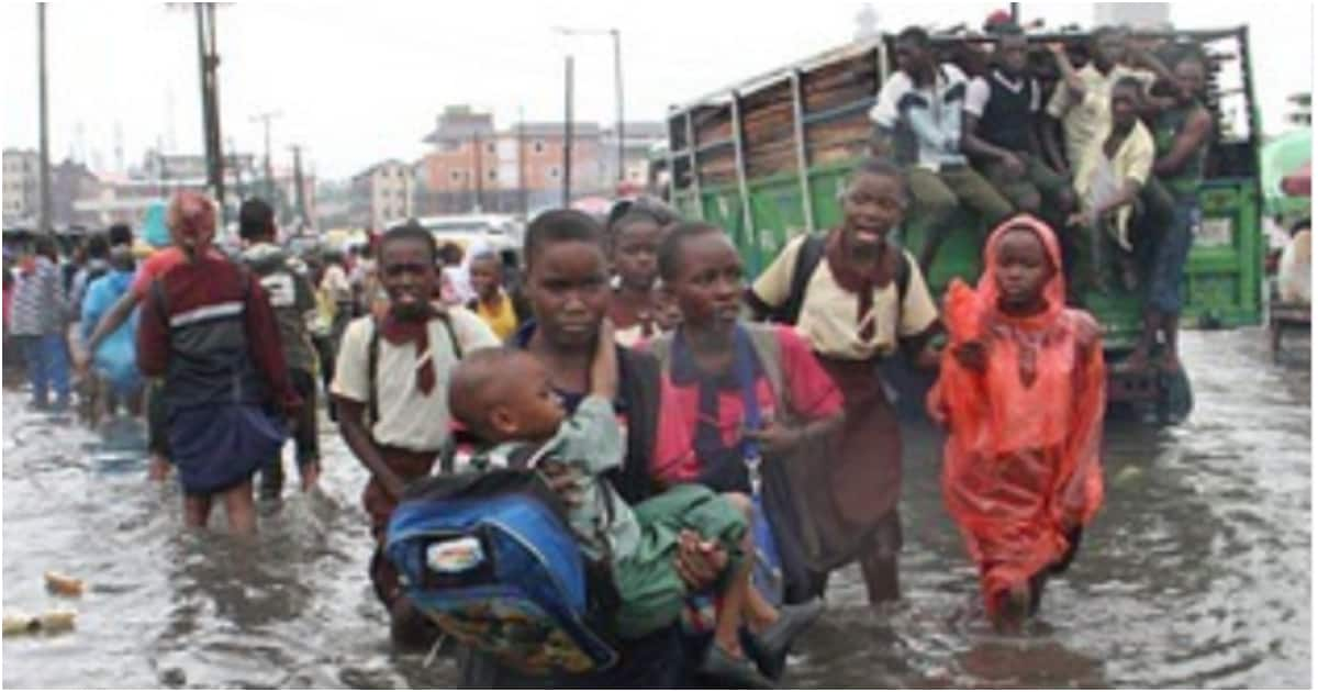 Heavy downpour forces students to walk home on a flooded street in Lagos state - Legit.ng