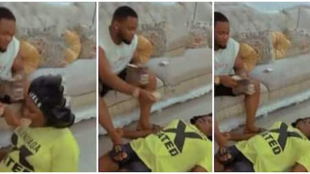 Nigerian man places foot on wife, puts wads of N1000 notes in her mouth to encourage her exercise in video