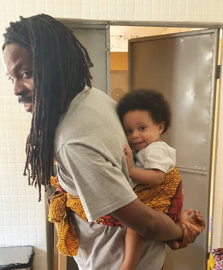 Working from home: Sierra Leone Minister feeds, carries 10-month-old daughter on his back during Zoom meeting