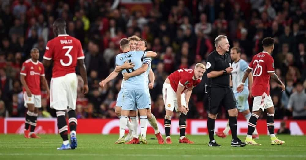 Manchester United players react as West Ham celebrate winning the English League Cup third round football match between Manchester United and West Ham United at Old Trafford in Manchester. (Photo by Oli SCARFF / AFP).