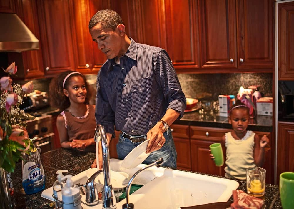 Obama helps his daughters wash their dishes after breakfast