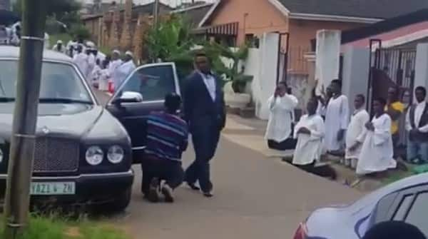 Photos and video of church members kneeling for pastor as he walks go viral