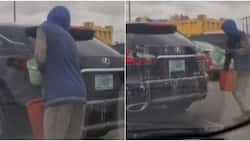 Mobile car wash: Massive reactions as young Nigerian man washes moving vehicle, video goes viral
