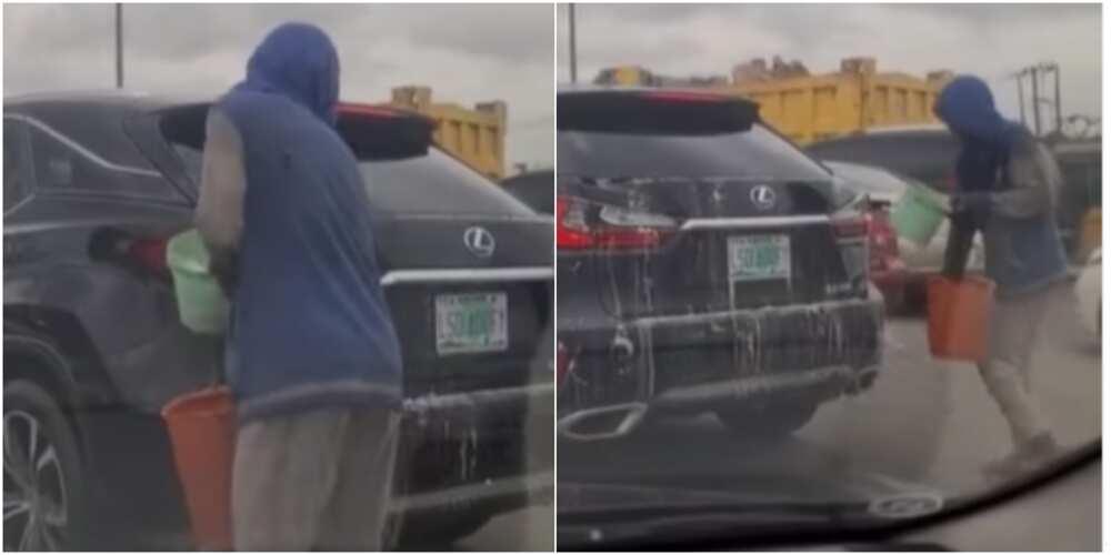 Man washing car in traffic