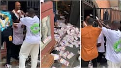 Friends storm man's house as he graduates, spray their whole compound with money in viral video