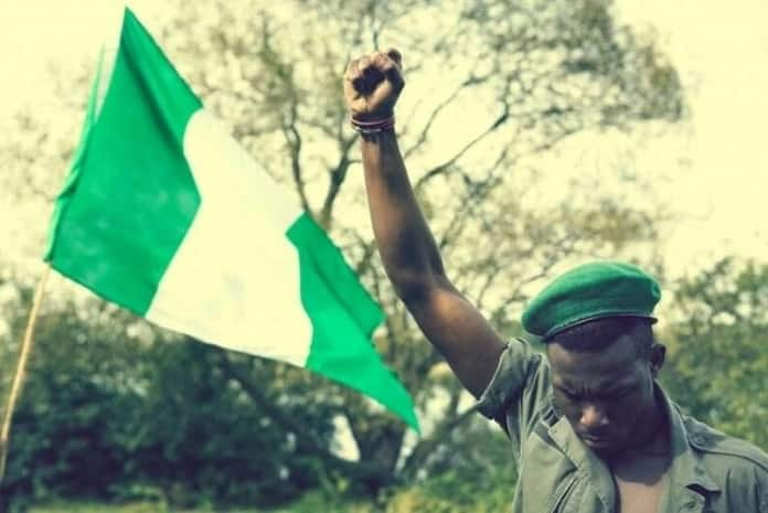 a young Nigerian man and a flag