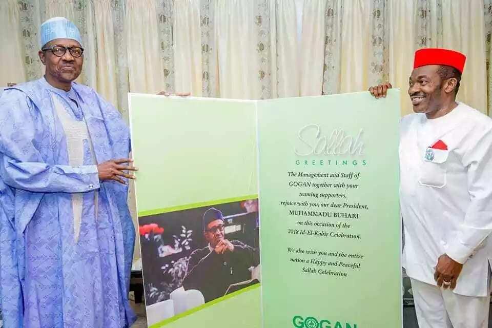 Chairman of Good Governance Ambassadors of Nigeria (GOGAN), Chief Felix Idiga, presents President Buhari with a Sallah greeting card. Credit: Facebook/Femi Adesina