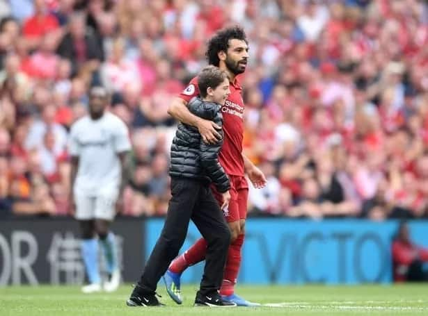 Mohamed Salah embraces young pitch invader