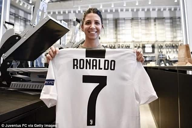 Juventus fans pose with Ronaldo's number 7 jersey at the club's jersey store