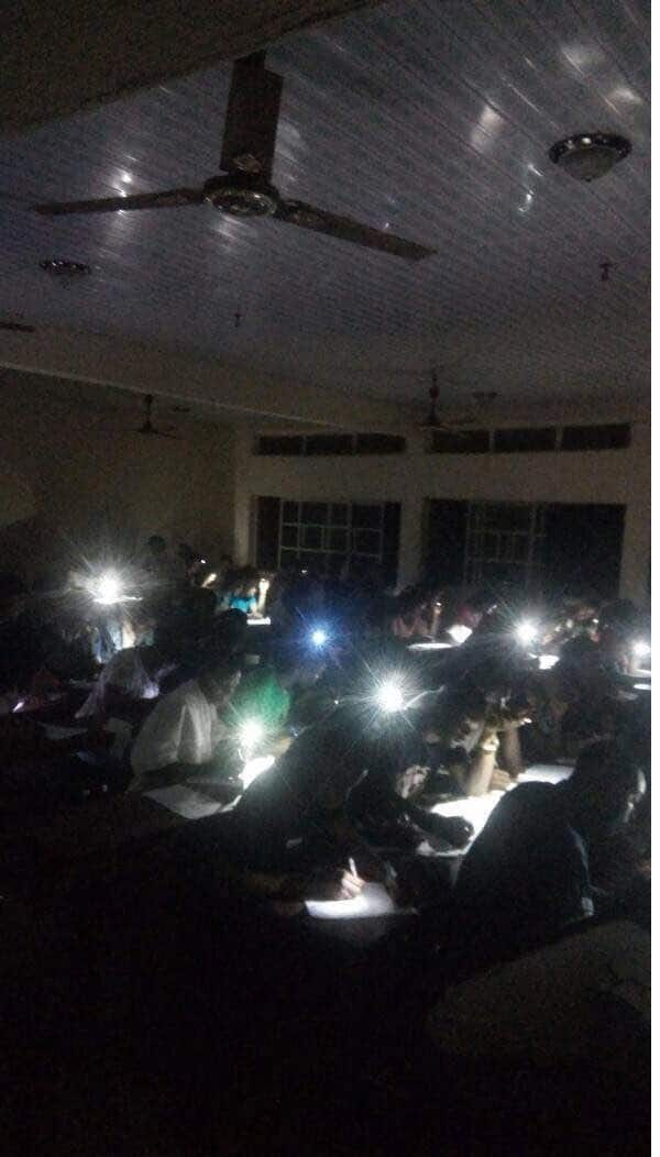 Oko polytechnic students write quiz at night with their phone torchlight