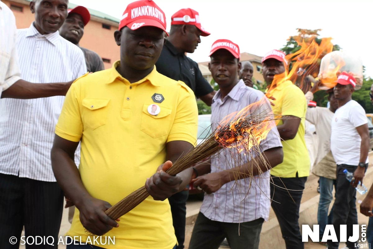 A supporter of Kwankwaso seen with a burning broom. Credit: Sodiq Adelakun