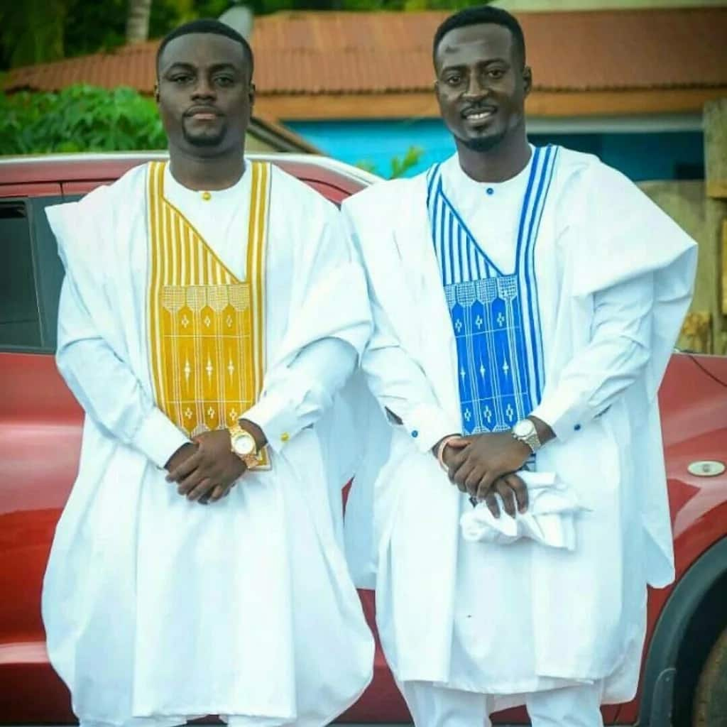 White Agbada styles for guys with blue and yellow ornaments