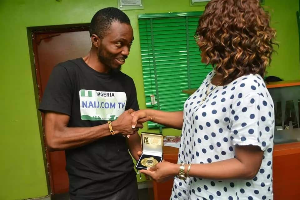 Damilare Okunola receiving the award for best street journalist from Sola Opesan Brown at Legit.ng's head office on July 28