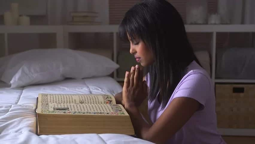 A girl praying with the Bible
