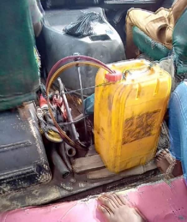 Man shows the fuel tank of a bus he boarded in Lagos