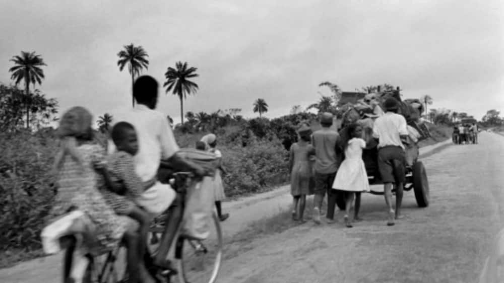 Photo of civilians fleeing Aba to go to Umuahia on August 28, 1968 as the Nigerian federal troops advance toward the city during the Biafran war. / AFP PHOTO / Francois Mazure