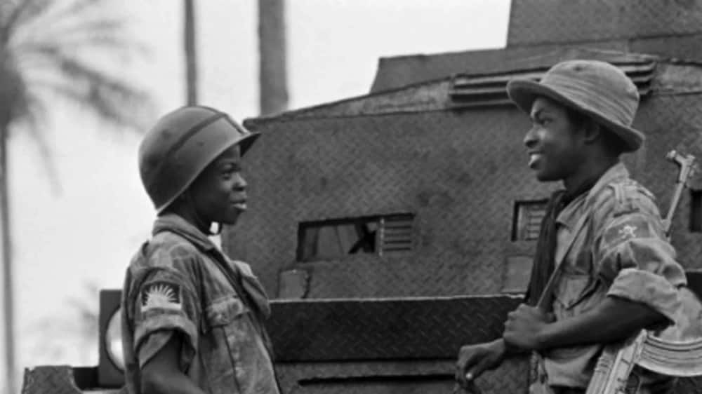 Moise, 14 (L) and Ferdinand, 16 (R), two children soldiers of the Biafran army during a discussion in Umuahia on August 31, 1968. AFP PHOTO/Francois Mazure